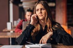 Коммерсантка сидя на таблице и говоря на телефоне в кафе бородатый фрилансер на заднем плане Стоковые Фотографии RF