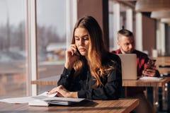 Коммерсантка сидя на таблице и говоря на телефоне в кафе бородатый фрилансер на заднем плане Стоковая Фотография