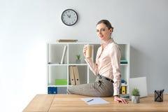 Коммерсантка сидя на таблице с кофе стоковая фотография rf