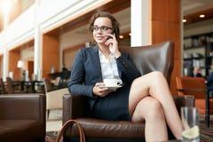 Коммерсантка сидя в кафе говоря на мобильном телефоне Стоковое Изображение
