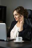 Коммерсантка сидя на ее рабочем месте в офисе с чашкой cof Стоковое фото RF