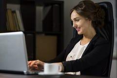 Коммерсантка сидя на ее рабочем месте в офисе с чашкой cof Стоковые Фото