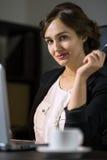 Коммерсантка сидя на ее рабочем месте в офисе с чашкой cof Стоковые Изображения RF