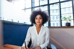 Коммерсантка сидя на ее столе и работая в офисе Стоковые Изображения RF