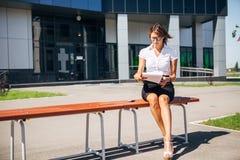 Коммерсантка сидя на стенде на обеденном времени и говоря телефон Стоковая Фотография