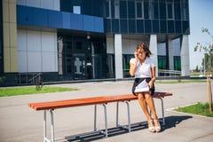 Коммерсантка сидя на стенде на обеденном времени и говоря телефон Стоковое Фото