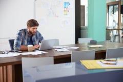 Коммерсантка сидя на столе в офисе работая на компьтер-книжке Стоковое фото RF