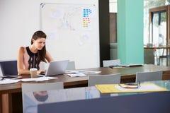 Коммерсантка сидя на столе в офисе работая на компьтер-книжке Стоковое Изображение RF