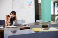 Коммерсантка сидя на столе в офисе работая на компьтер-книжке Стоковая Фотография RF
