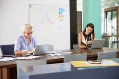 Коммерсантка сидя на столе в офисе работая на компьтер-книжке Стоковая Фотография