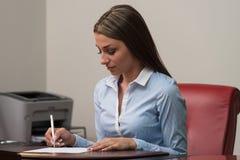 Коммерсантка сидя на столе офиса подписывая контракт Стоковое Фото