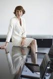 Коммерсантка сидя на столе переговоров Стоковые Фотографии RF