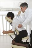 Коммерсантка сидя на стуле массажа, Стоковые Изображения RF