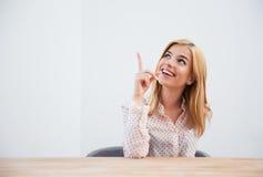 Коммерсантка сидя на таблице и указывая палец вверх Стоковые Изображения RF