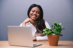 Коммерсантка сидя на таблице с компьтер-книжкой Стоковое Изображение