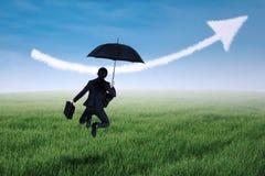 Коммерсантка скача с зонтиком стоковая фотография