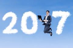 Коммерсантка скача с компьтер-книжкой и 2017 Стоковые Изображения RF