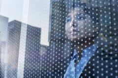 Коммерсантка смотря вне через окно, отражение города на стекле стоковое фото rf