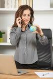 Коммерсантка смотря глобус мира и говоря на телефоне Стоковое Фото