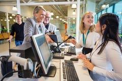 Коммерсантка смотря женский персонал на регистрации авиапорта стоковые изображения rf