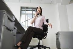 Коммерсантка смотря отсутствующий пока говорящ на телефоне в офисе Стоковые Изображения RF