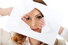 Коммерсантка смотря через бумажный лист Стоковое Изображение