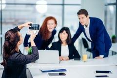 Коммерсантка снимая ее коллег на камере мобильного телефона Стоковое Изображение