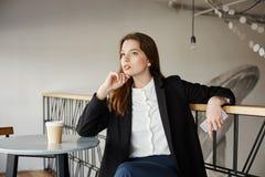 Коммерсантка составляя идею повысить ее компанию Сторон-съемка привлекательной модной женщины сидя в кафе, полагаясь Стоковые Фотографии RF