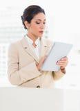 Коммерсантка стоя за ее стулом используя цифровую таблетку стоковое изображение