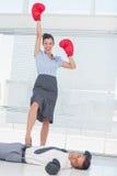 Коммерсантка стоя на нанесенном поражение gl бокса бизнесмена нося Стоковые Изображения RF