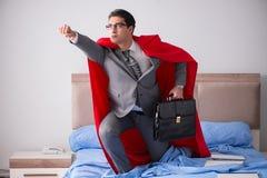 Коммерсантка супергероя работая в кровати стоковое фото