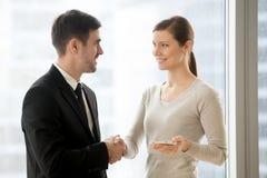 Коммерсантка счастливого handshaking бизнесмена усмехаясь с таблеткой, Стоковая Фотография