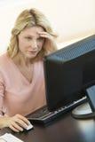 Коммерсантка с головой в руках используя компьютер на столе Стоковая Фотография
