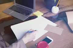 Коммерсантка с листом документов бумажным в офисе просторной квартиры современном, работая на портативном компьютере Деятельность Стоковое Изображение RF