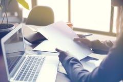Коммерсантка с листом документов бумажным в офисе просторной квартиры современном, коммерсантка с листом документов бумажным в оф стоковое фото rf