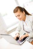 Коммерсантка с компьтер-книжкой в офисе Стоковое Изображение RF