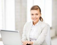 Коммерсантка с компьтер-книжкой в офисе Стоковая Фотография