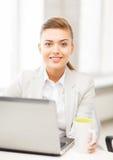 Коммерсантка с компьтер-книжкой в офисе Стоковое Изображение