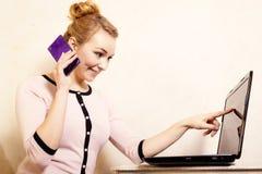 Коммерсантка с компьтер-книжкой касающего экрана телефона Стоковое Изображение
