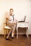 Коммерсантка с компьтер-книжкой касающего экрана телефона Стоковое Фото