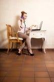 Коммерсантка с компьтер-книжкой касающего экрана телефона Стоковые Фотографии RF