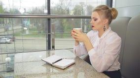 Коммерсантка с кофе smartphone выпивая видеоматериал