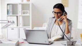 Коммерсантка с пусковой площадкой вызывая на телефоне на офисе акции видеоматериалы