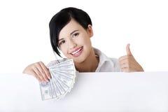 Коммерсантка с пустыми деньгами удерживания доски знака. Стоковое Изображение RF
