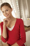 Коммерсантка с рукой на Chin стоя в лобби офиса Стоковые Изображения