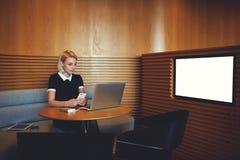 Коммерсантка с сет-книгой сидит в coworking внутренний близко экран с насмешкой вверх по космосу экземпляра для рекламировать Стоковые Изображения RF