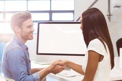 Коммерсантка тряся руки с сотрудником пока работающ на компьютере Стоковое Изображение