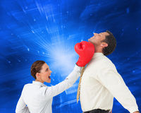 Коммерсантка ударяя бизнесмена с перчатками бокса Стоковое Изображение RF