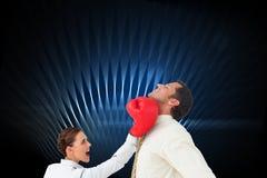 Коммерсантка ударяя бизнесмена с перчатками бокса Стоковое Изображение
