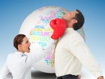 Коммерсантка ударяя бизнесмена с перчатками бокса Стоковые Изображения